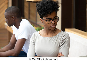 Black unhappy couple sitting on sofa separately at each other