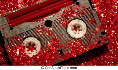 Black video cassette on the background of red glitter