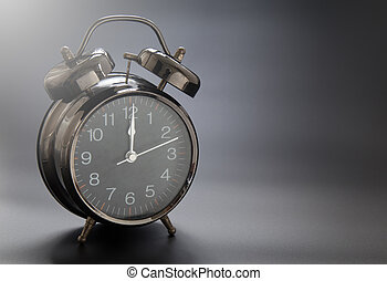 Black vintage alarm clock on black background