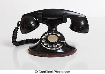 Black, vintage rotary phone on  white