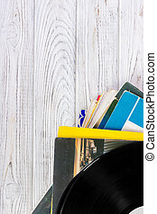 Black vinyl records on the wooden table, selective focus with copy space. Top view