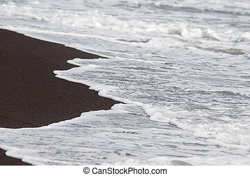 Black volcanic sand and waves on the beach in Legazpi, Philippines