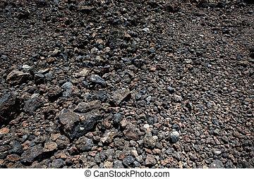 Black volcanic stones soil texture in Lanzarote