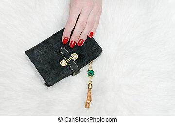 Black wallet in female hand. White fur on background