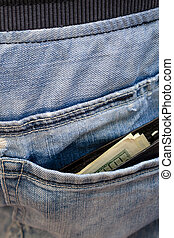 Black wallet with money, sticking out of the back pocket of the jeans. Nonchalance concept. Vertical.