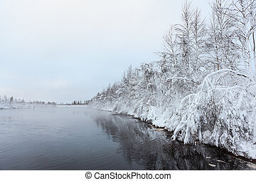 Black water of lake with snow-covered trees on shore