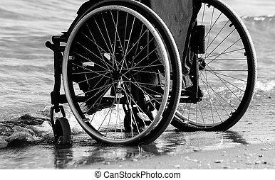 wheelchair beside the sea on sandy beach