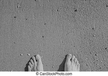 black white barefoot on sand