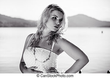Black & White Photo of a Model standing in front of a lake