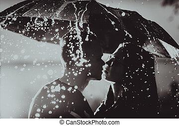 black white photo young couple standing under a dark umbrella