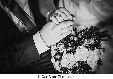 Black white  photography hands of bride and groom on the bouquet