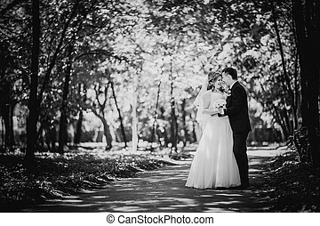Black white photography happy couple bride and groom embracing they stand in a forest full length