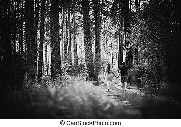 Black white photography romantic young couple go and holding hands on background summer