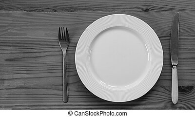 black white White plate and knife with a fork are served on a wooden table. view from above.