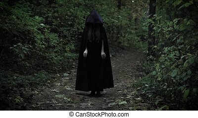 black witch is wearing black coat with hood sliding on a...