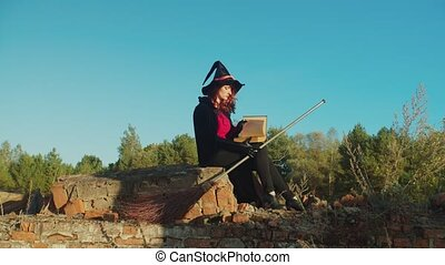 Black witch with broom sitting on ruined breastwork - ...