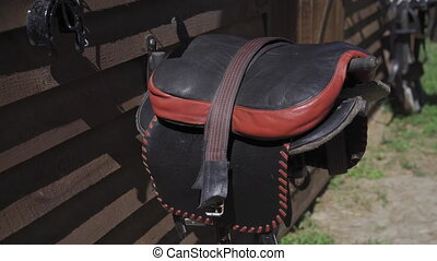 Black with red striped leather handmade saddles hang on a wooden pallet wall near the stall ready for sledging on horses with a camera slide down panorama. Riding lessons concept. 4k UHD.
