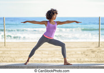 Black woman, afro hairstyle, doing yoga in warrior asana in ...