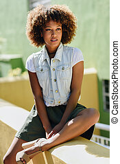 Black woman, afro hairstyle, wearing casual clothes in urban background