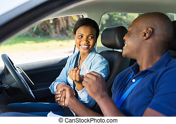 black woman being handed driver's license by driving...
