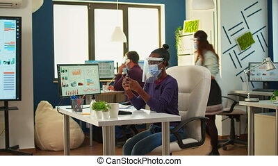 Black businesswoman browsing using smartphone sitting in office room wearing face mask and visor while team doing stategy. Multiethnic coworkers working respecting social distance in financial company