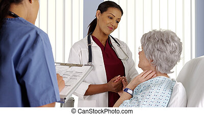 Black woman doctor holding elderly patient's hand in hospital room