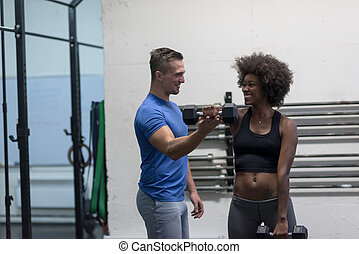 black woman doing bicep curls with fitness trainer - young...