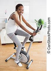 Black woman doing exercise bike with headphones