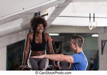 black woman doing parallel bars Exercise with trainer