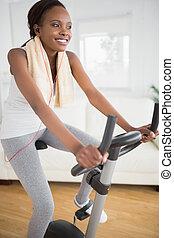 Black woman doing sport on an exercise bike