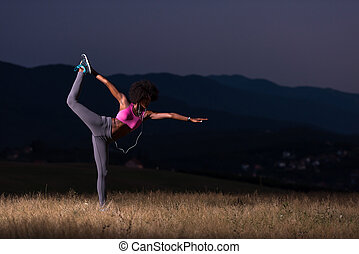 black woman doing yoga in the nature