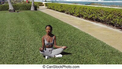 Black woman doing yoga on lawn - Attractive young ethnic...