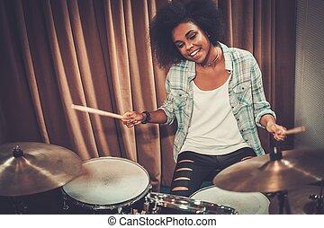 Black woman drummer in a recording studio