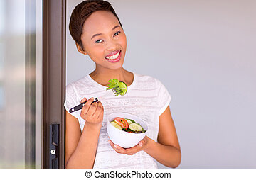 black woman eating green salad
