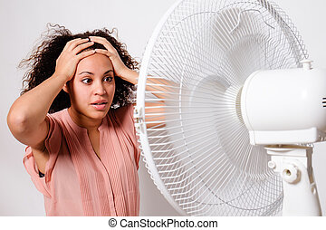 Black woman feeling hot and sitting in front of an electric...