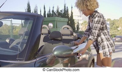 Young sporty mixed-race woman dressed in plaid men's shirt white top shorts and white socks opens the car door and get into the convertible in slow motion.