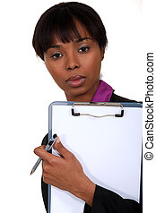 Black woman holding a clipboard.
