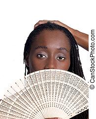 Black woman holding wooden fan before face