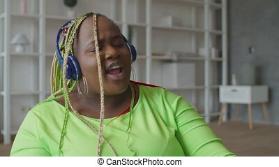 Black woman in headphones enjoying music at home - Charming ...