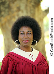 Black woman in red church robes outdoors portrait