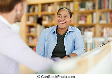 Black woman laughing at joke of friend in library