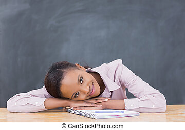 Black woman leaning her head on desk while smiling