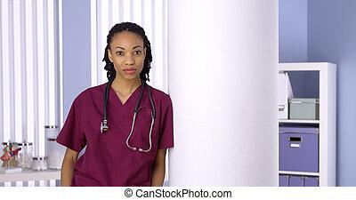 Black woman nurse standing in office