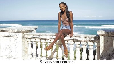 Black woman on fence at sea - Cheerful young pretty ethnic...