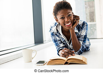 black woman reading a book next to a big window with natural light