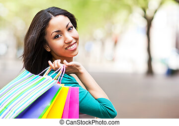 Black woman shopping - A shopping black woman carrying...