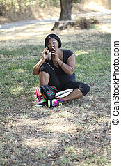 Black Woman Sitting on Ground Outdoors Smoking