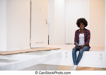 black woman sitting on stairs at home