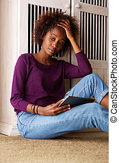 Black woman sitting with digital tablet