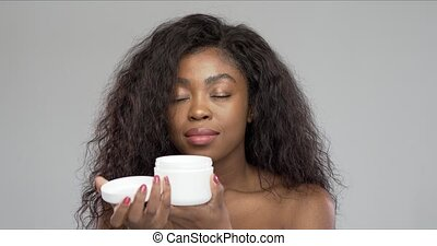 Black woman smelling cream with closed eyes - African ...